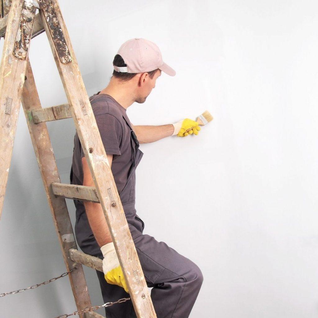 Man målar en vägg vit